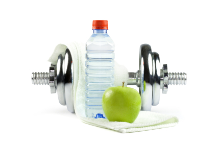 Metal dumbell with green apple, bottle of water and towel